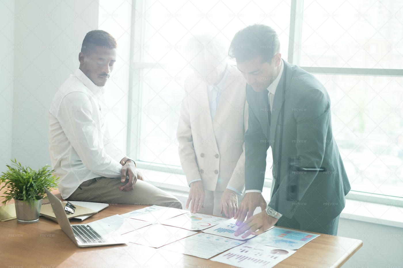 Serious Analysts Comparing Graphs: Stock Photos