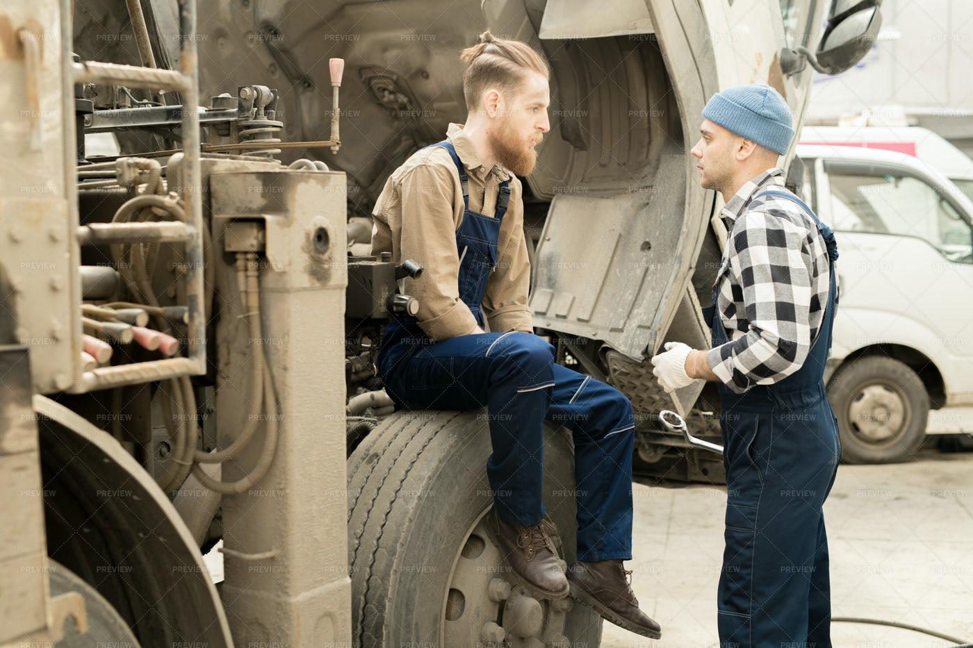 Mechanics Discussing Repair Of...: Stock Photos