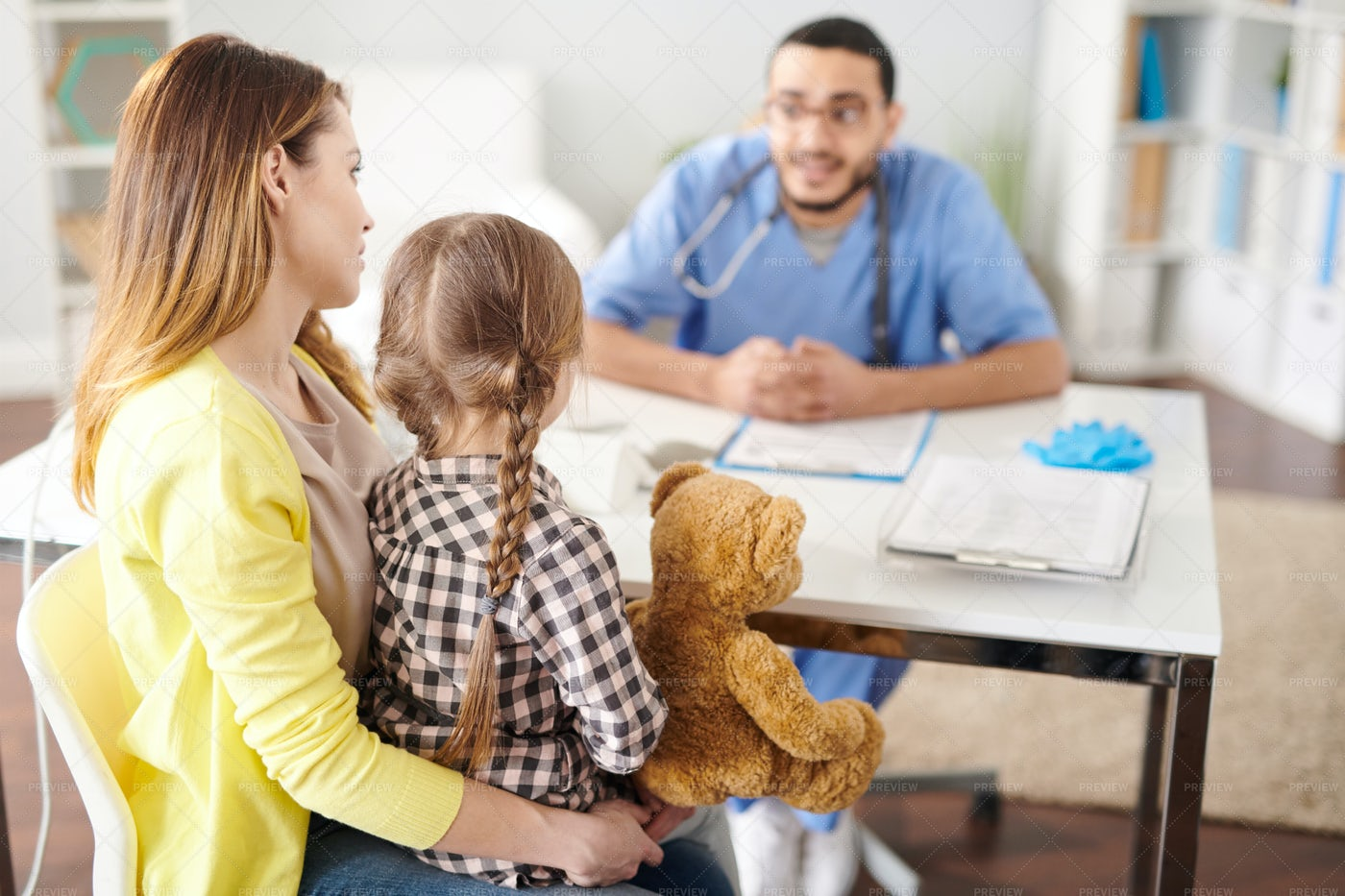 Mother With Little Girl In Doctors...: Stock Photos
