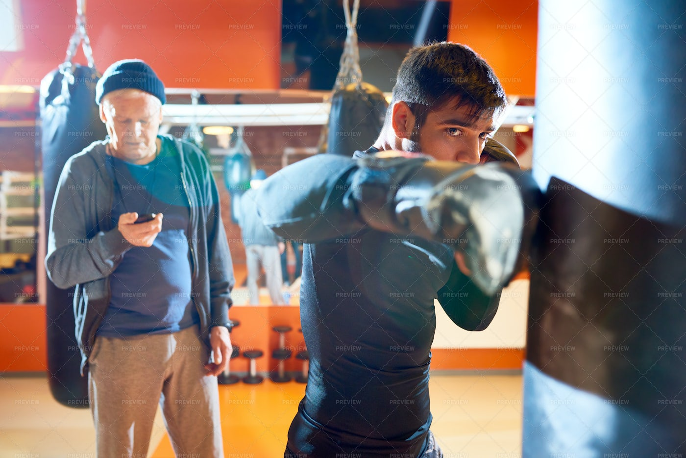 Man Boxing Bag With Trainer On...: Stock Photos