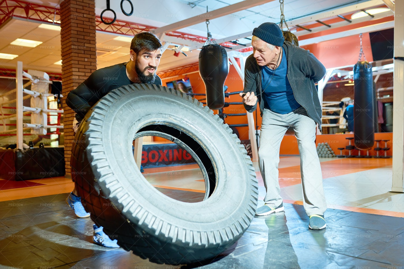 Sportsman Flipping Tyre With Coach...: Stock Photos