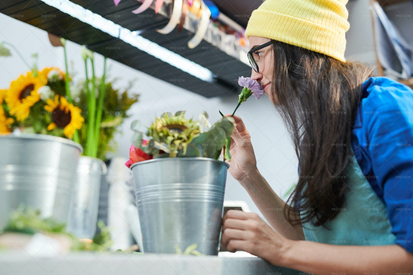 Young Woman Smelling Flowers In...: Stock Photos