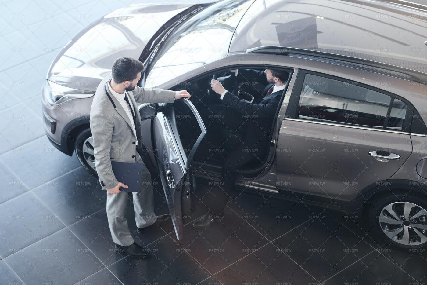 Car Salesman Opening Door To Client: Stock Photos