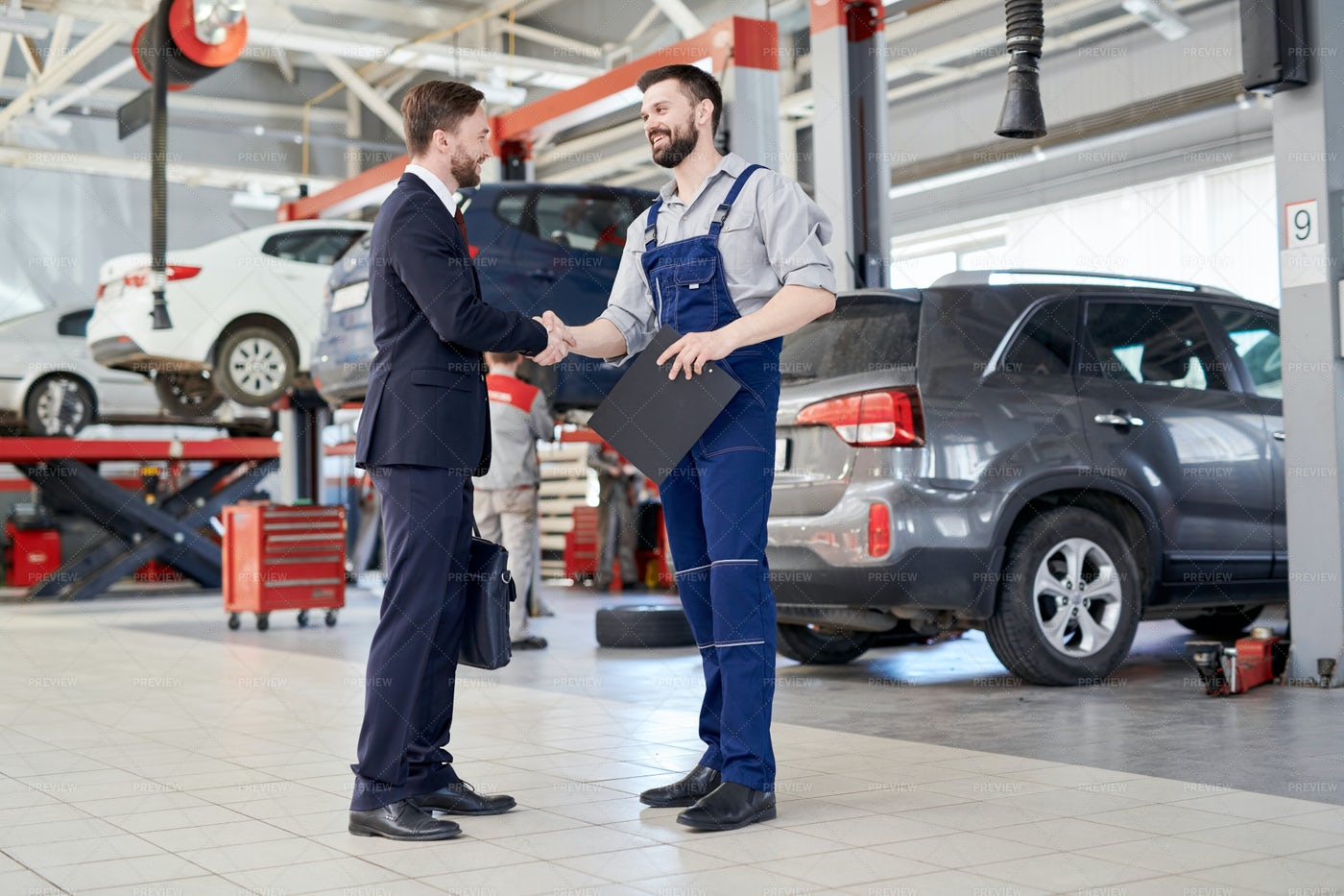 Worker Shaking Hands With Client In...: Stock Photos