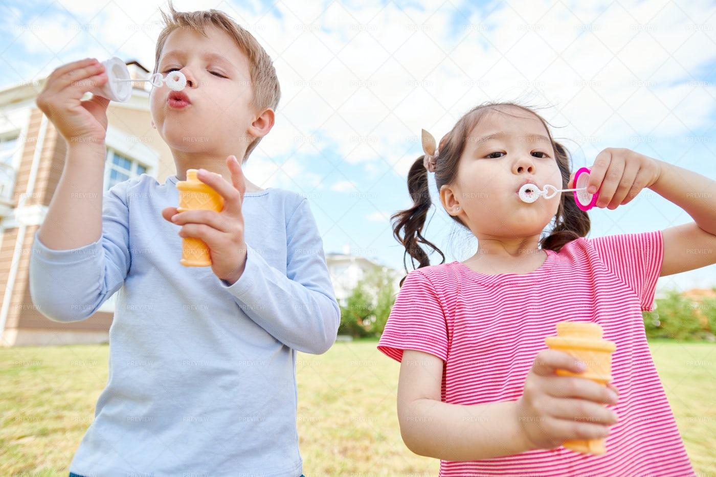 Happy Children Blowing Bubbles: Stock Photos