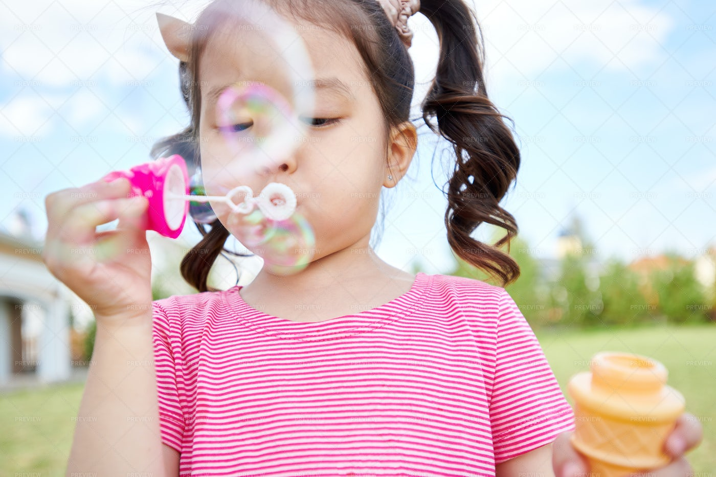 Cute Asian Girl Blowing Bubbles...: Stock Photos