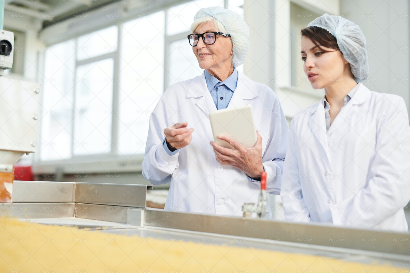 Two Women Overseeing Production At...: Stock Photos