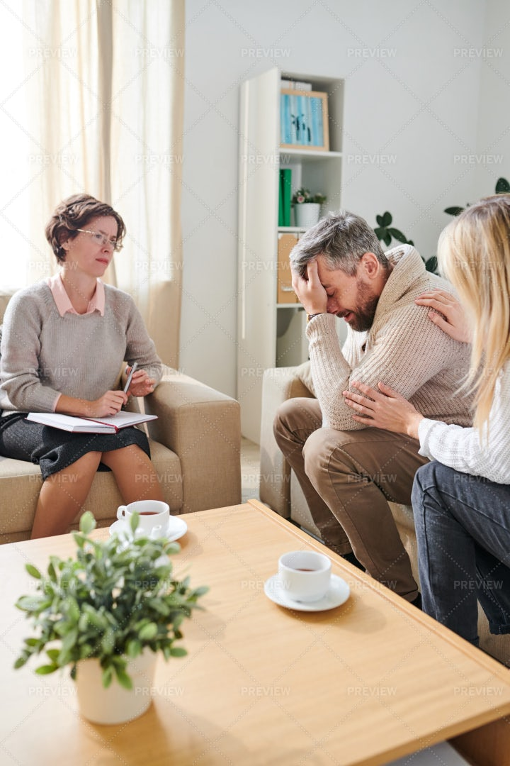 Frustrated Man Crying While Wife...: Stock Photos