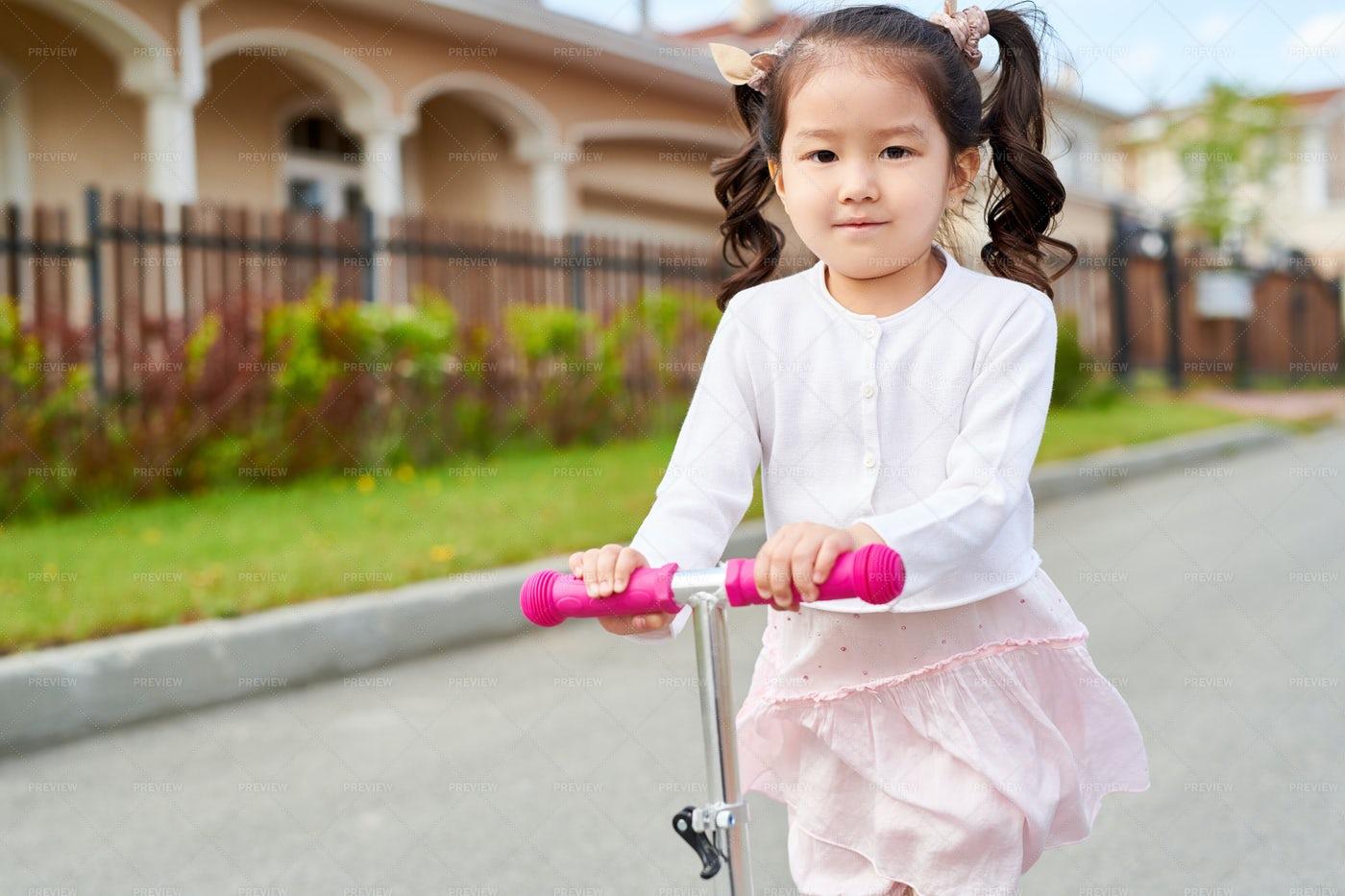 Little Asian Girl Riding Scooter: Stock Photos