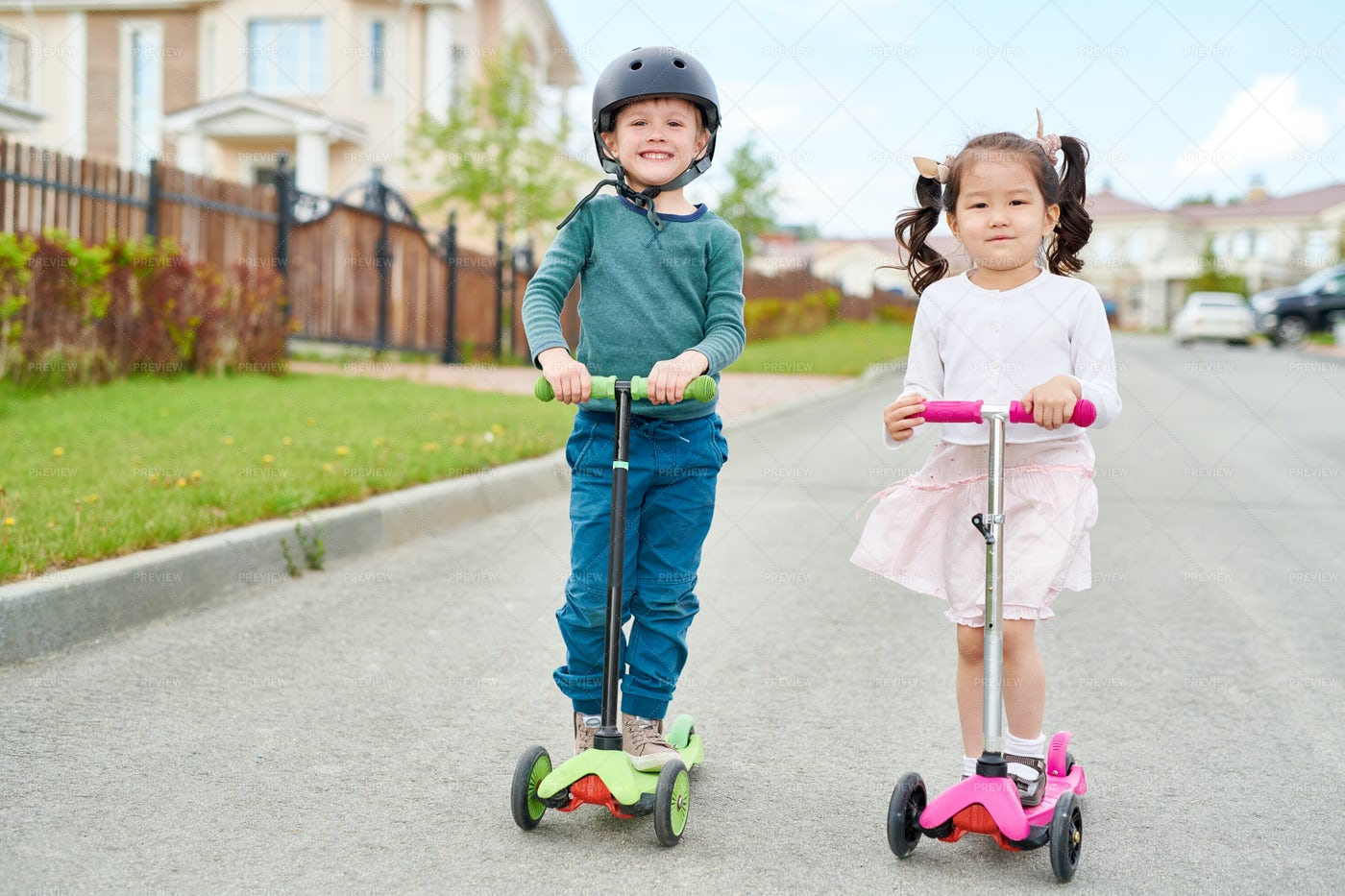 Two Cute Children Riding Scooters: Stock Photos