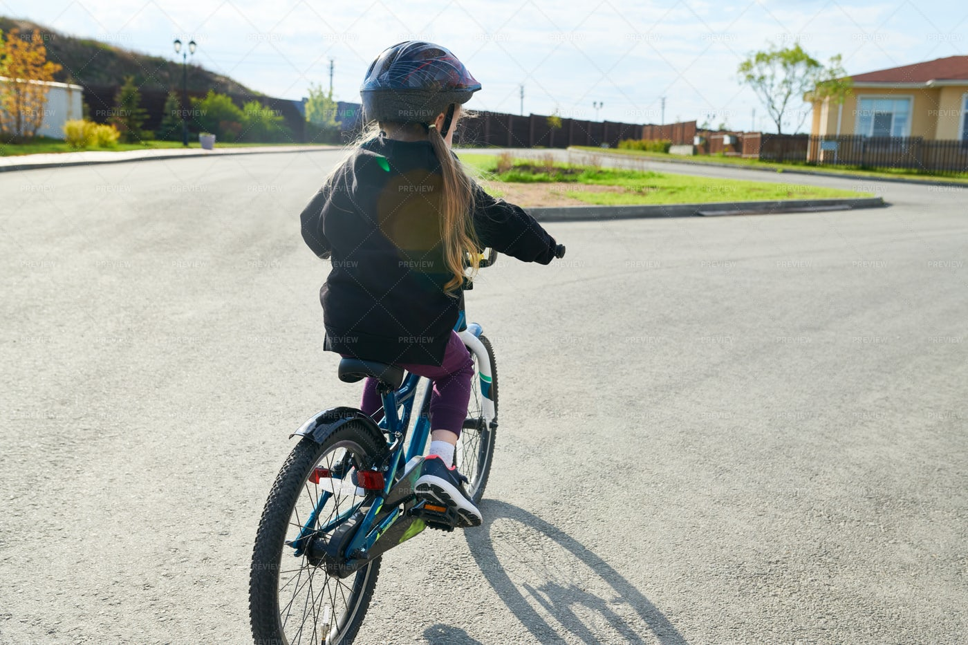 Girl Riding Bicycle In Sunlight: Stock Photos
