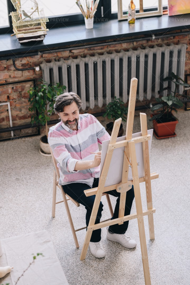 Mature Artist Painting At Easel: Stock Photos