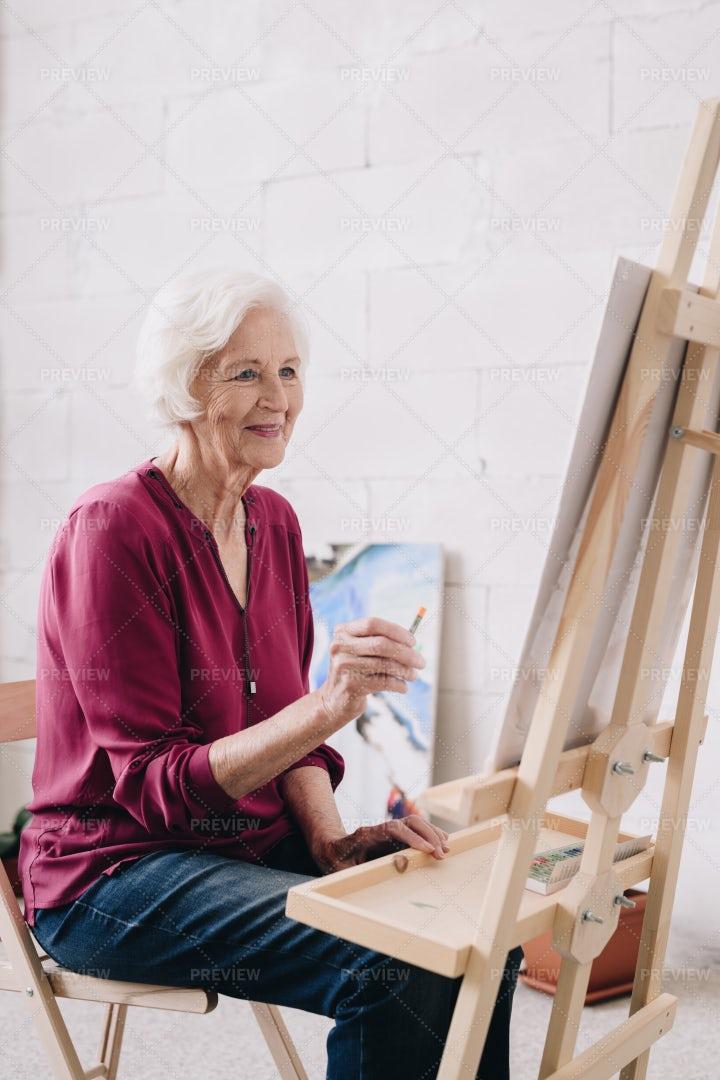 Smiling Senior Woman Painting At...: Stock Photos