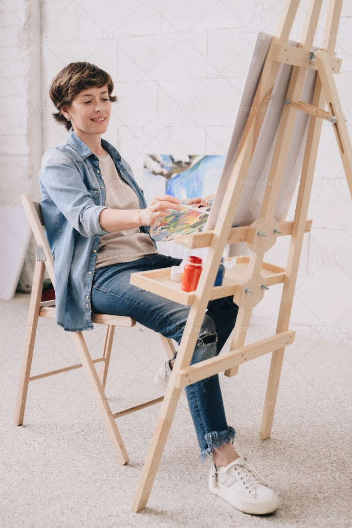 Female Artist Painting At Easel: Stock Photos