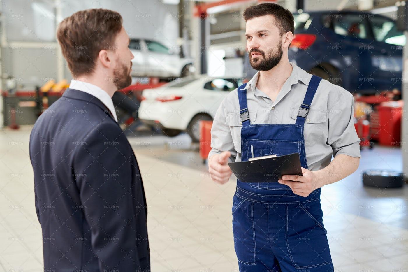Modern Mechanic Talking To Client: Stock Photos