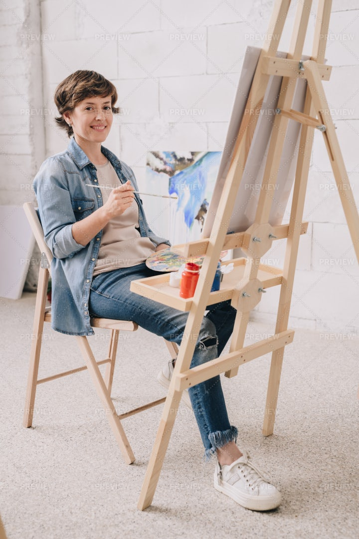 Smiling Female Artist By Easel: Stock Photos