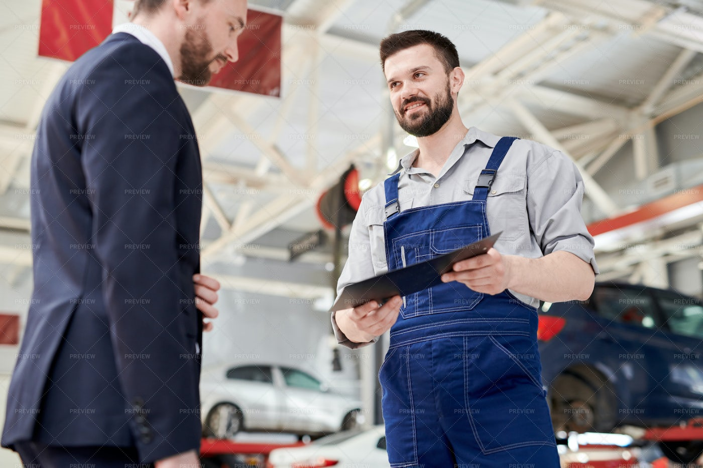 Smiling Mechanic Giving Contract To...: Stock Photos