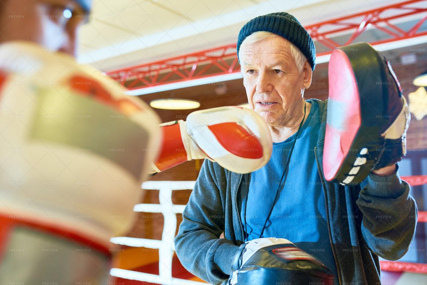 Senior Coach Training Boxer In Ring: Stock Photos