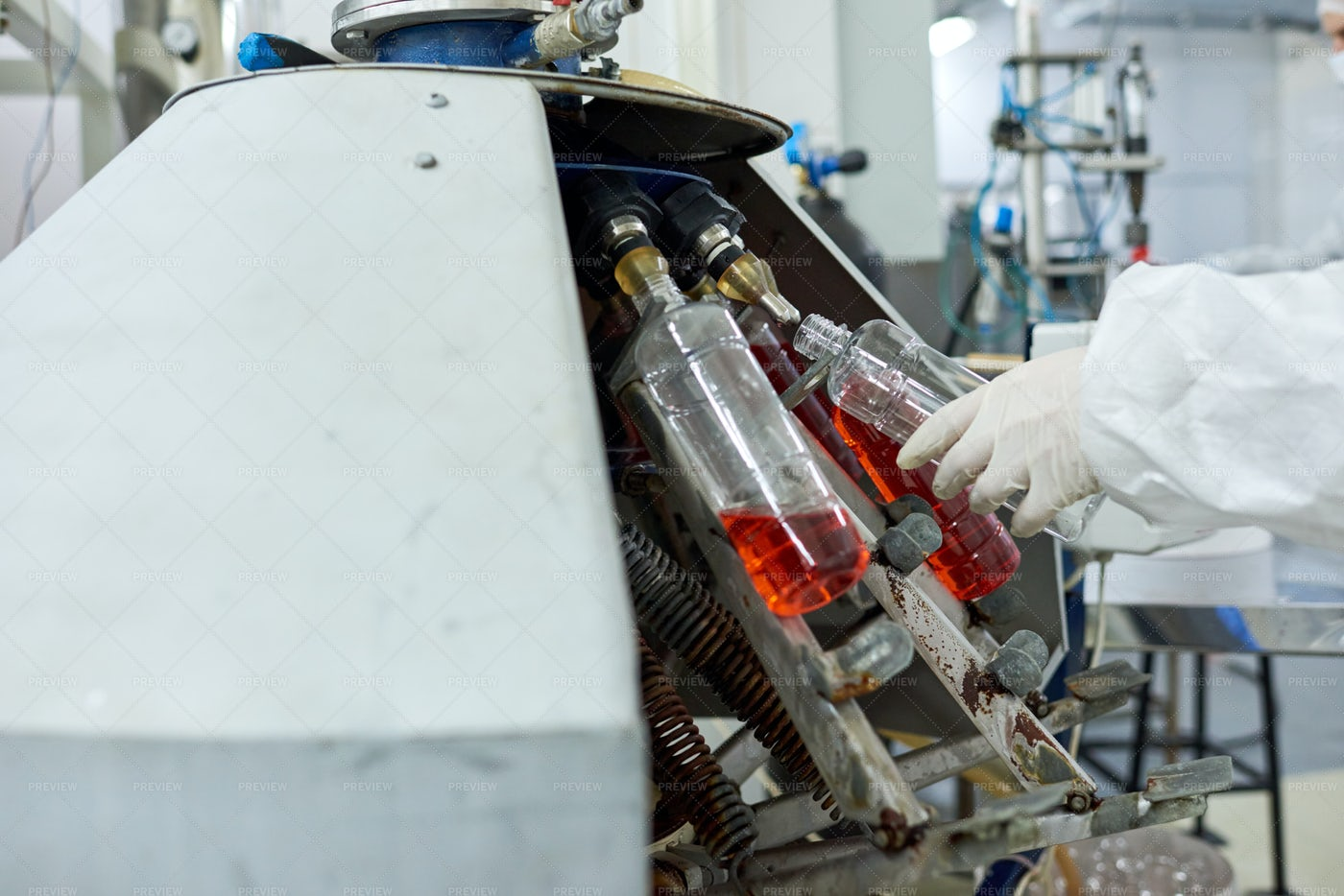 Factory Worker Filling Bottle With...: Stock Photos