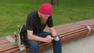 Redhead Hipster With Phone And Skateboard: Stock Footage