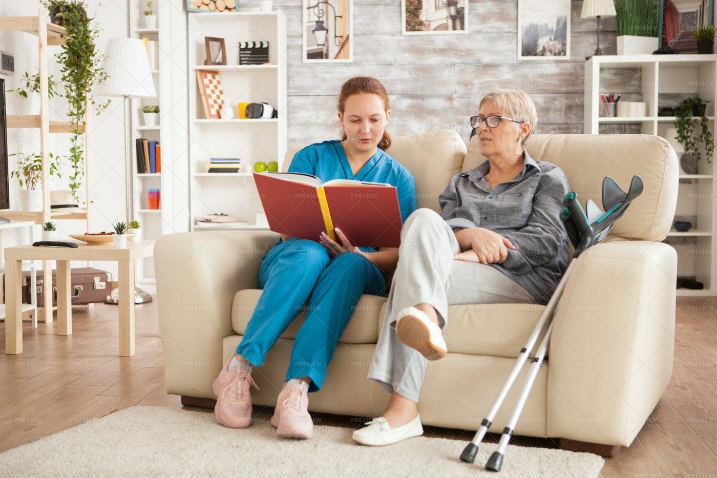 Caregiver Reading A Book: Stock Photos
