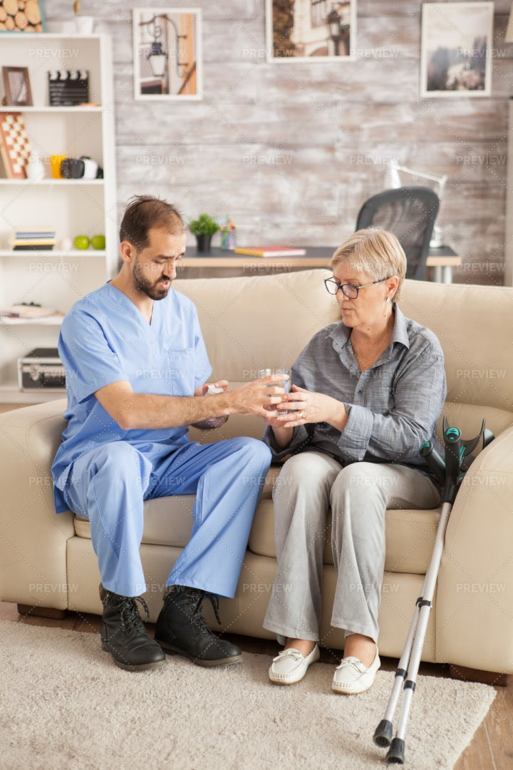 Giving Medication To  Senior Woman: Stock Photos