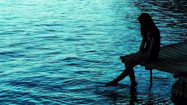 Young Girl Silhouette Near The Ocean On A Dock: Stock Video