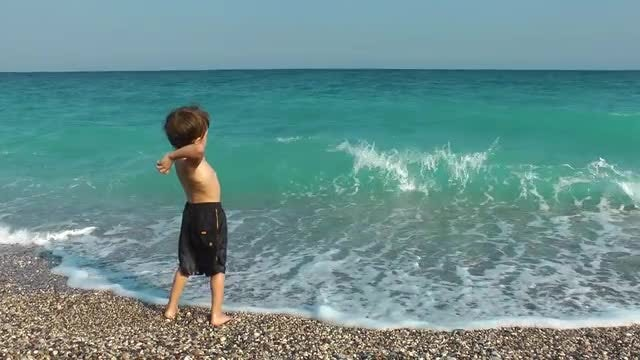 Boy Throwing Stones To The Sea: Stock Video
