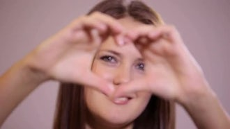 Girl Makes a Heart shape with Her Hands: Stock Video