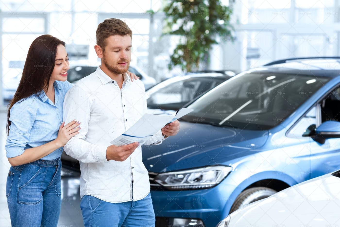 Looking At Car Catalogue: Stock Photos