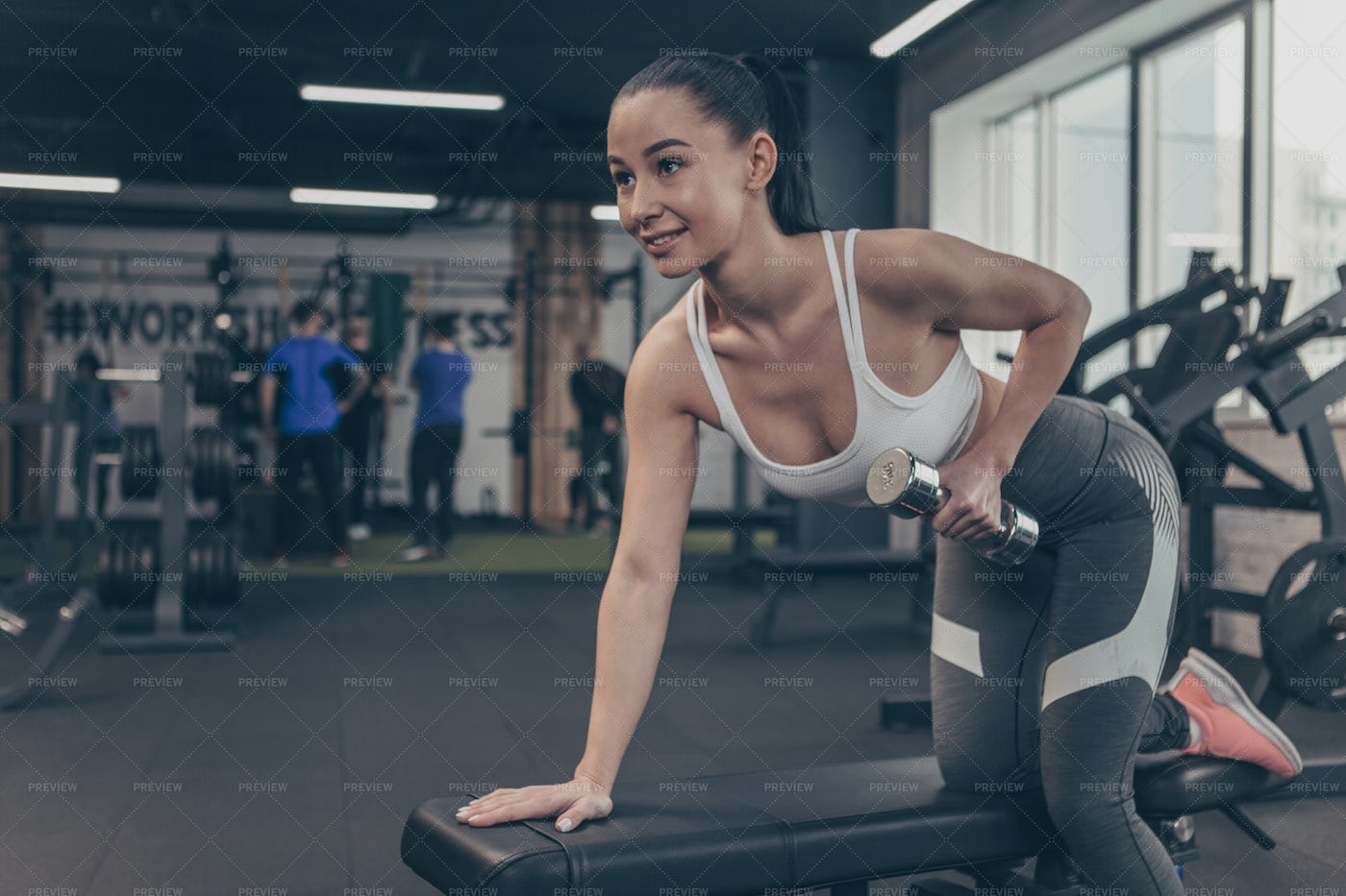 Woman Performs Dumbbell Rows: Stock Photos