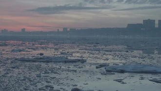 Icy City River Under Pink Sunset in Winter: Stock Video