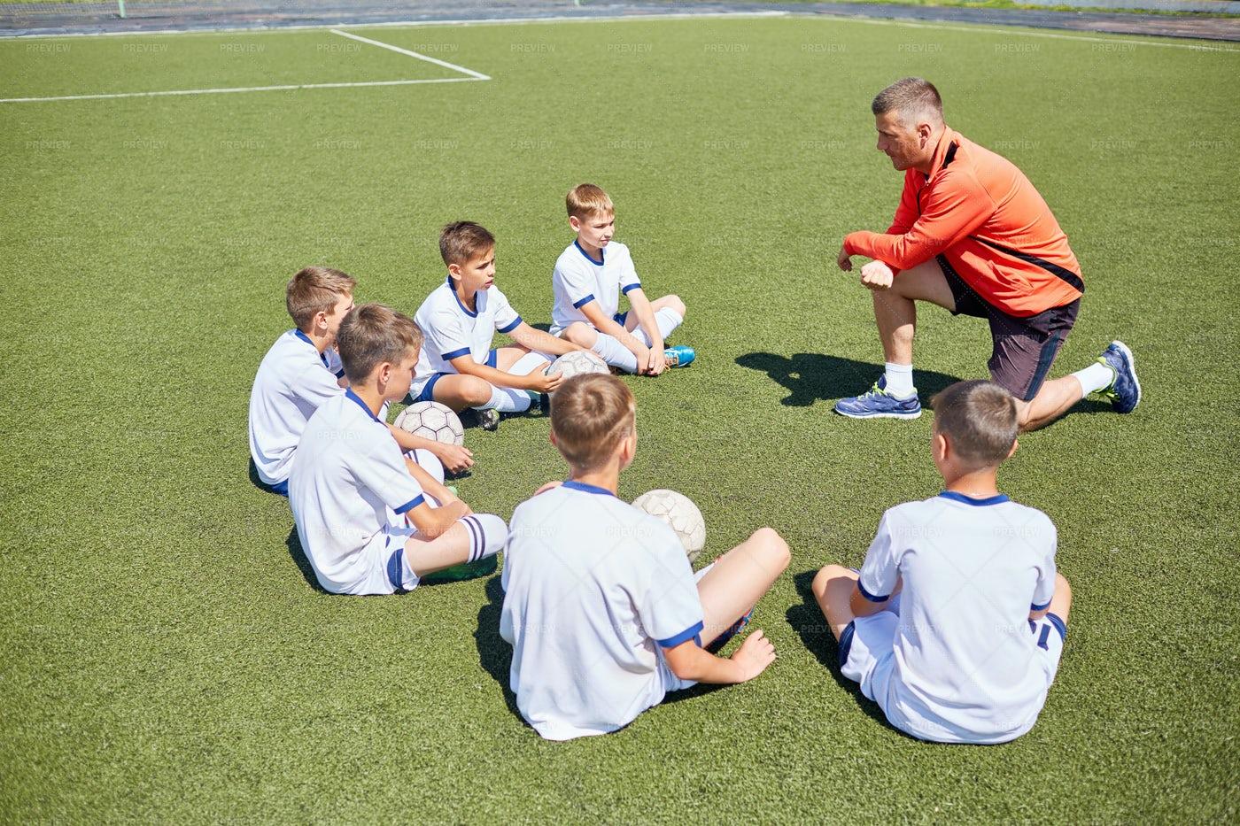 Coach Teaching Junior Football Team: Stock Photos