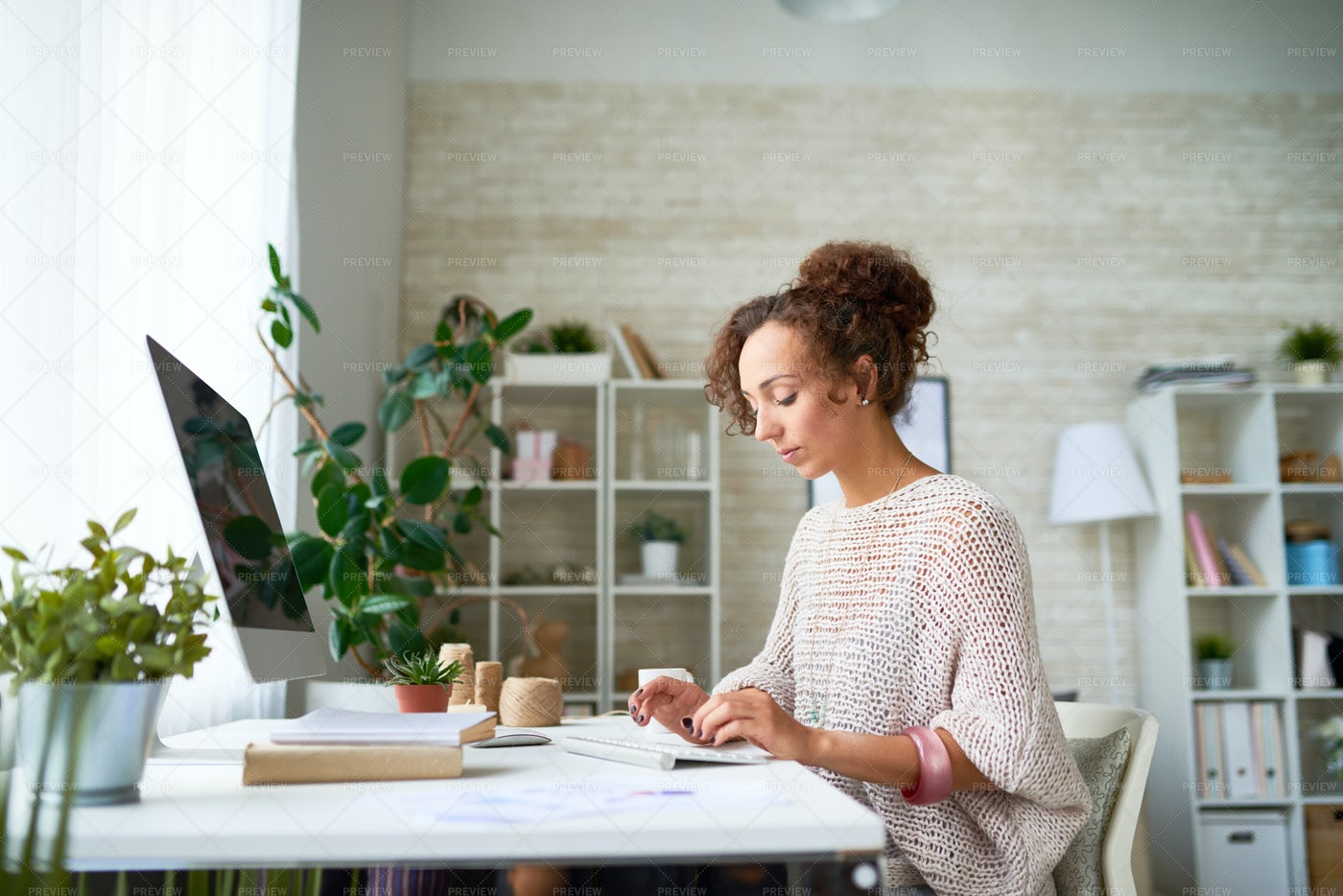 Pretty Young Woman Working From...: Stock Photos
