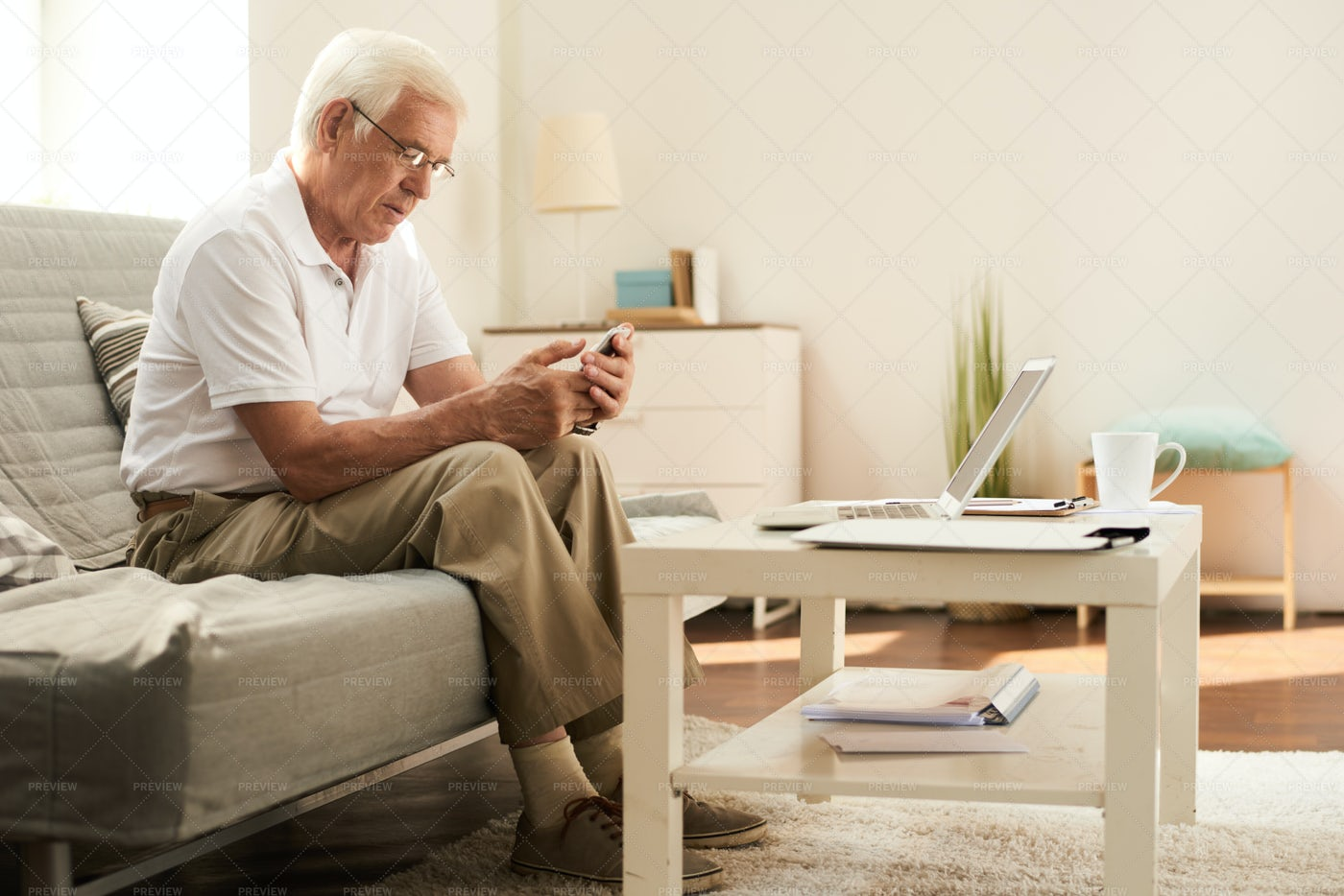 Senior Man Using Smartphone At Home: Stock Photos