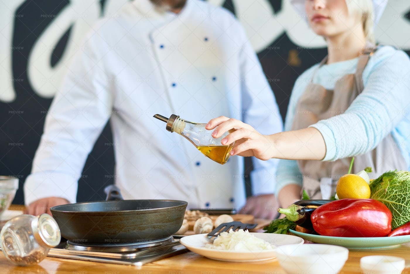 Two Cooks Adding Olive Oil To Dish...: Stock Photos