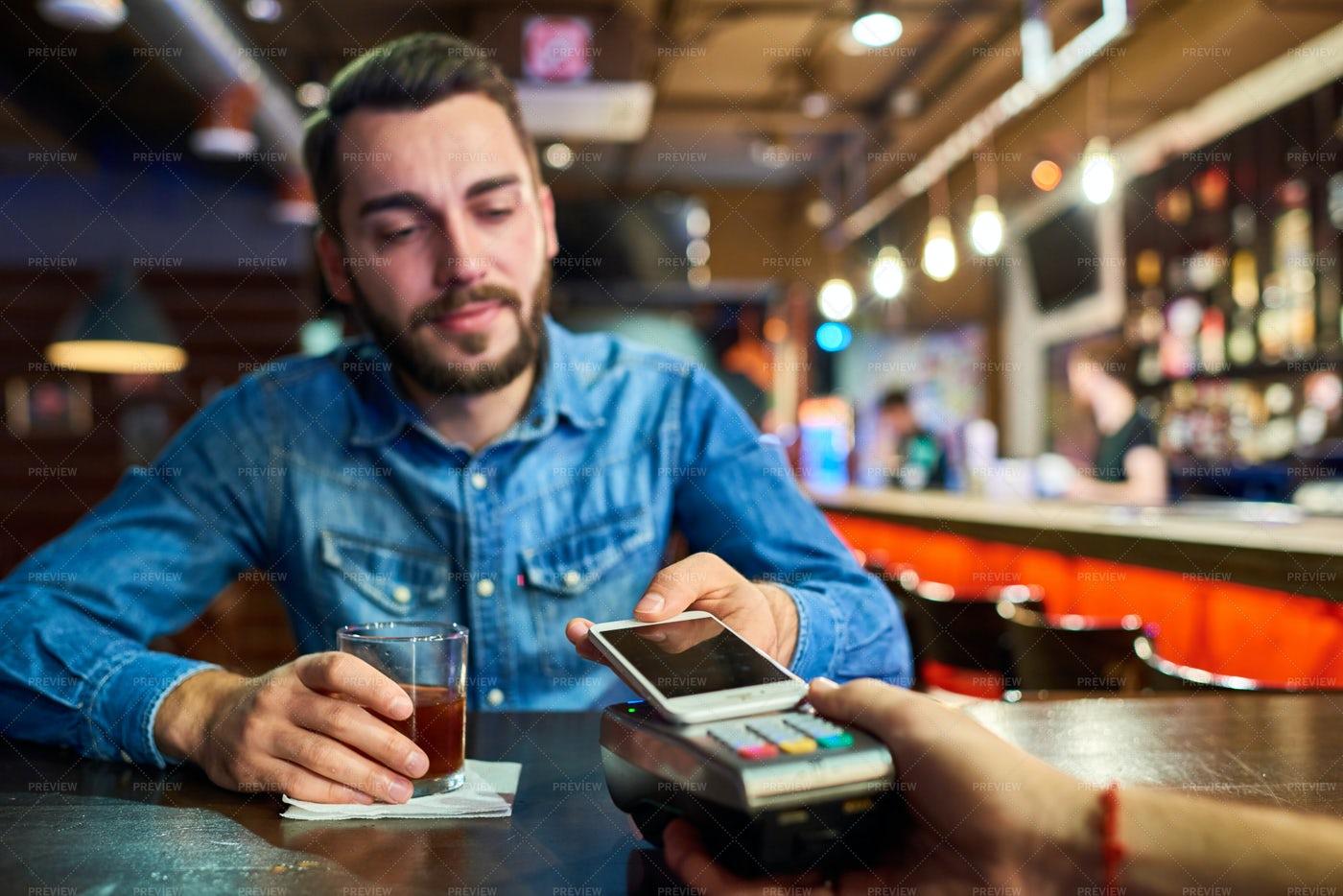 Drunk Man Paying Via NFC In Bar: Stock Photos