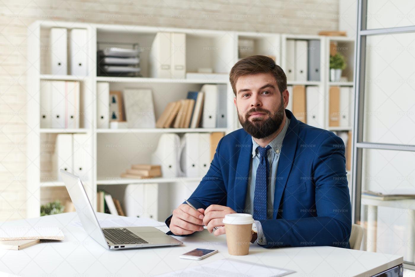 Modern Businessman Posing At Desk...: Stock Photos
