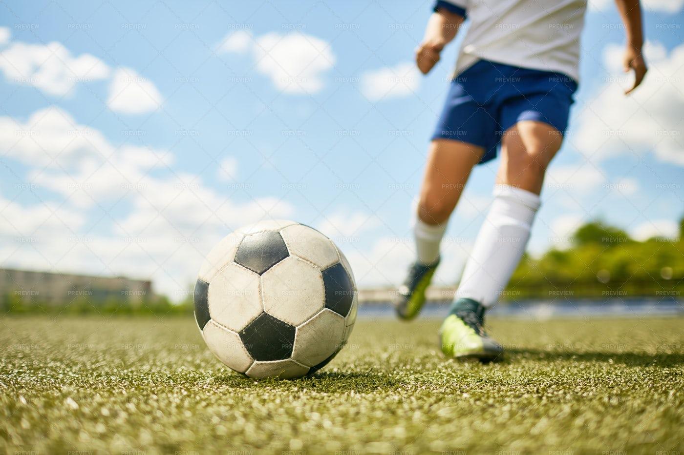 Boy Kicking Ball In Football: Stock Photos