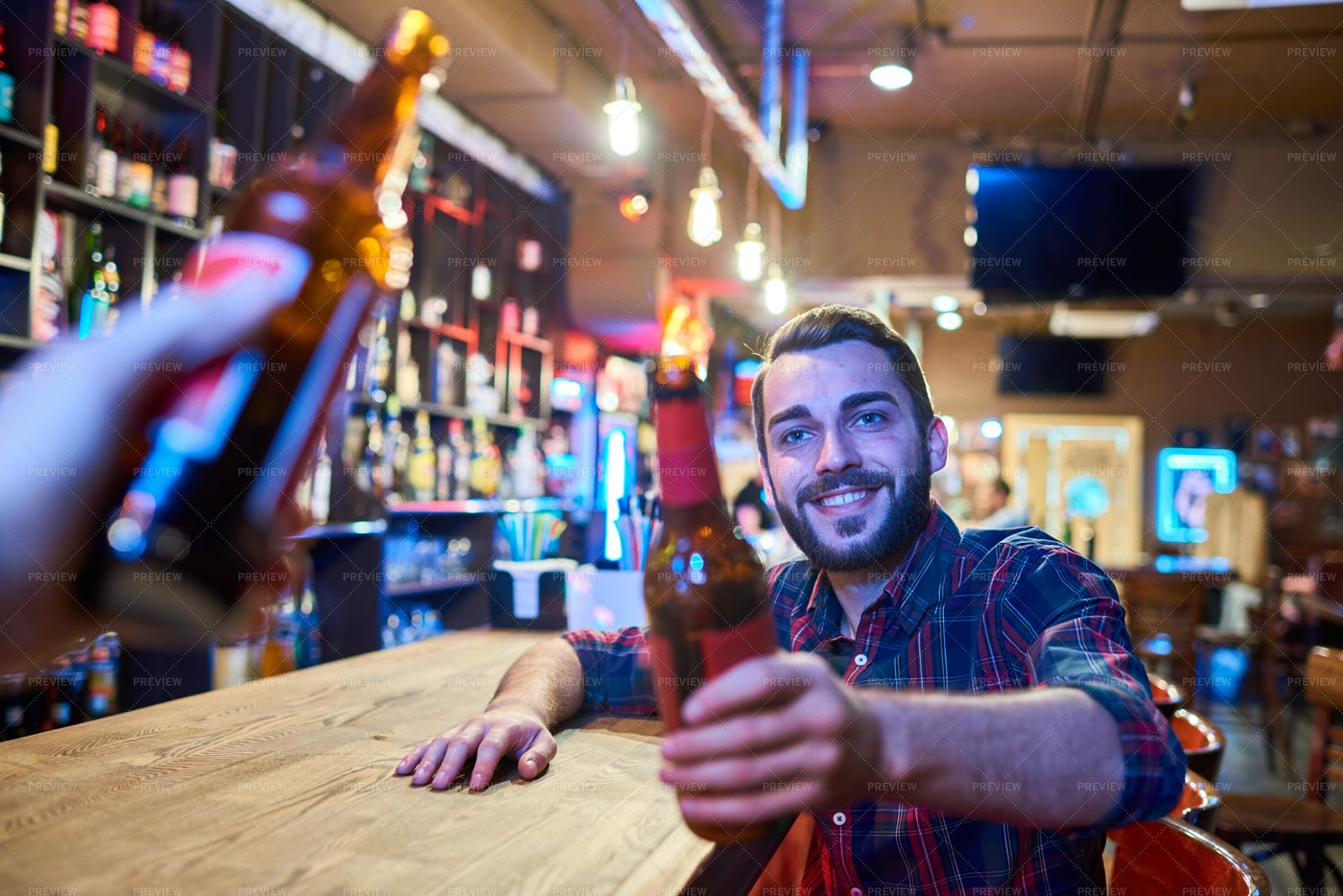 Happy Young Man Clinking Bottles At...: Stock Photos