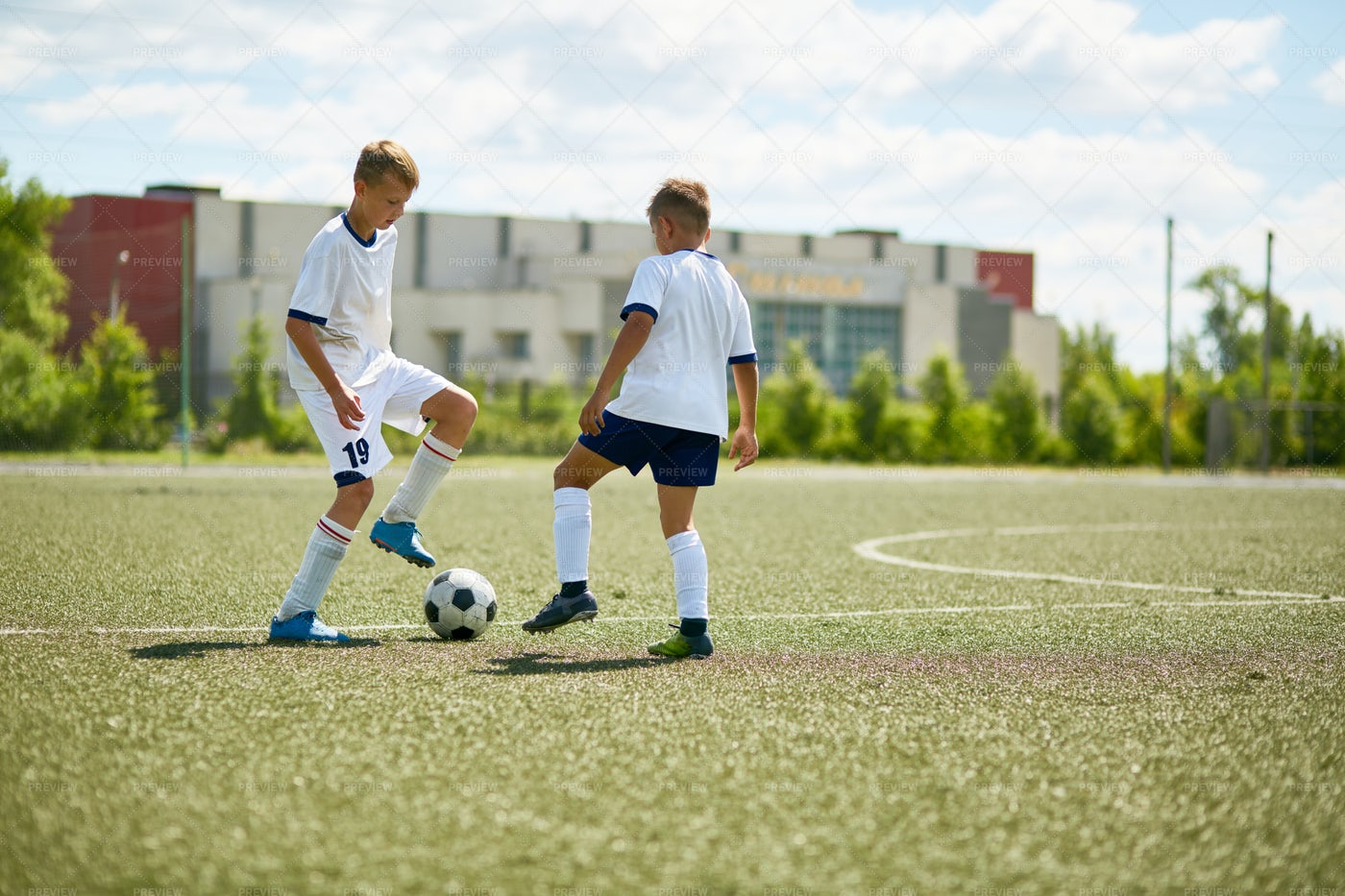 Two Boys Playing On  Football Field: Stock Photos