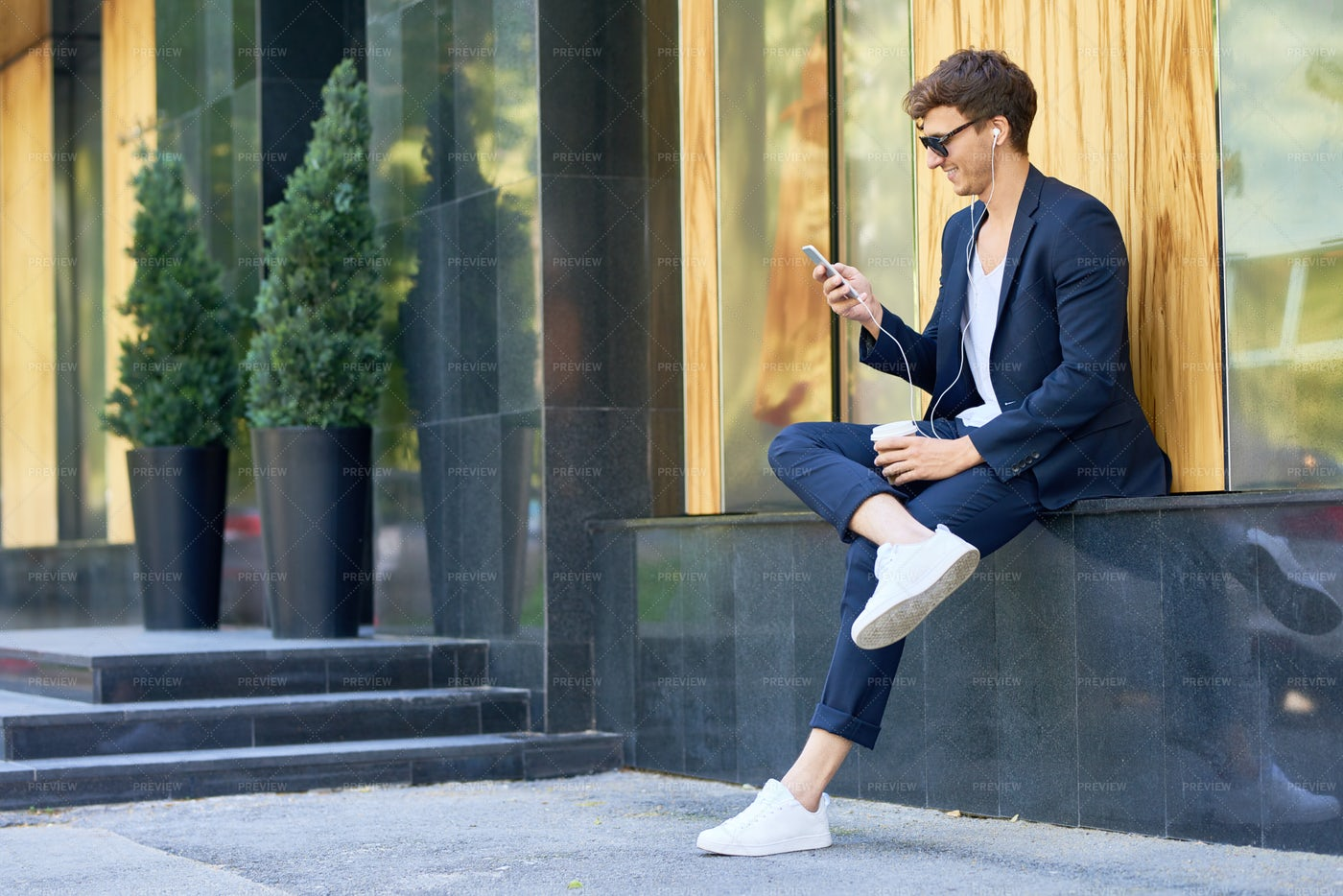 Trendy Young Man Relaxing With...: Stock Photos