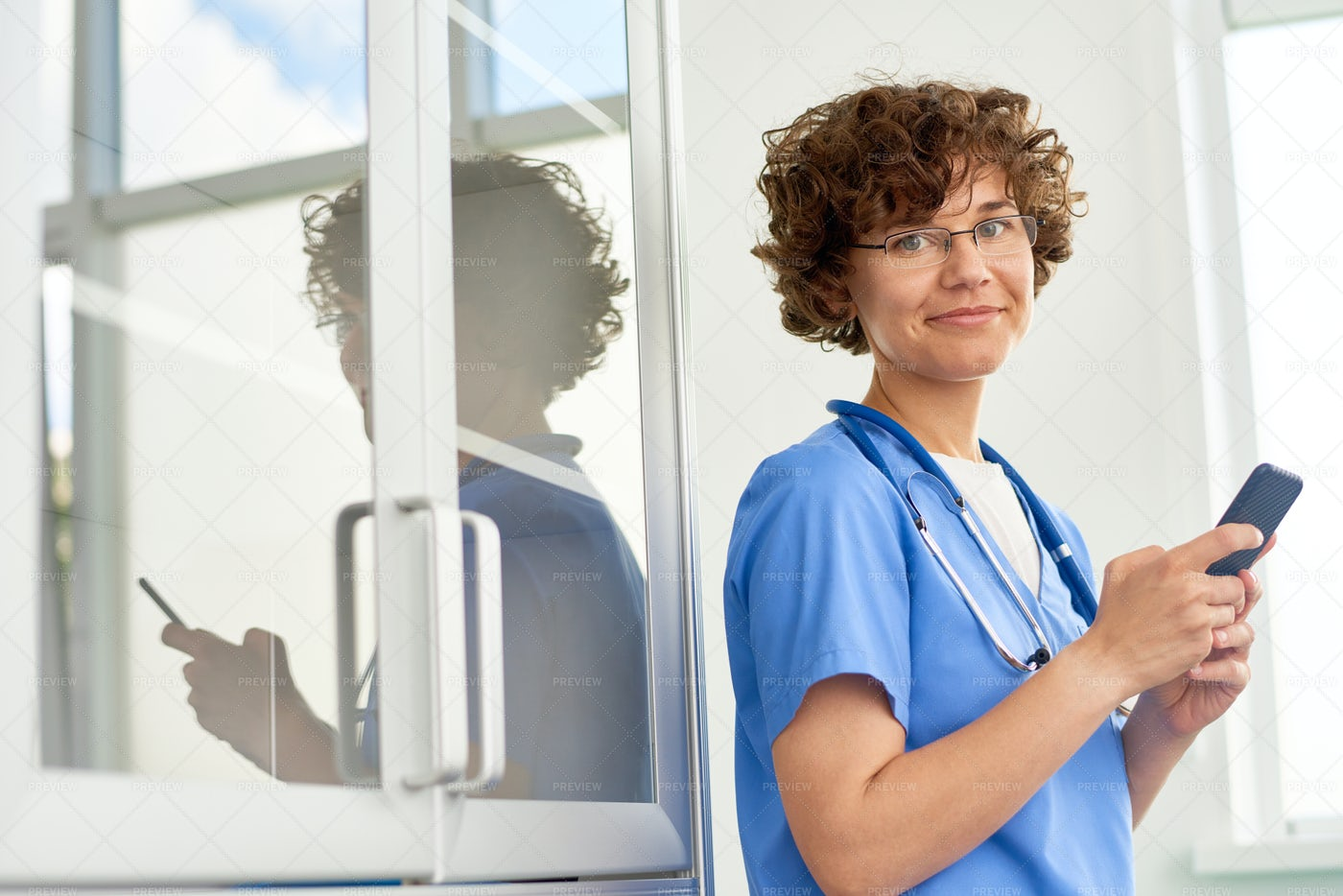 Curly Physician Using Smartphone: Stock Photos
