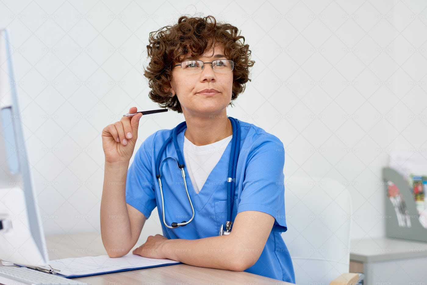 Thinking Female Doctor At Desk In...: Stock Photos