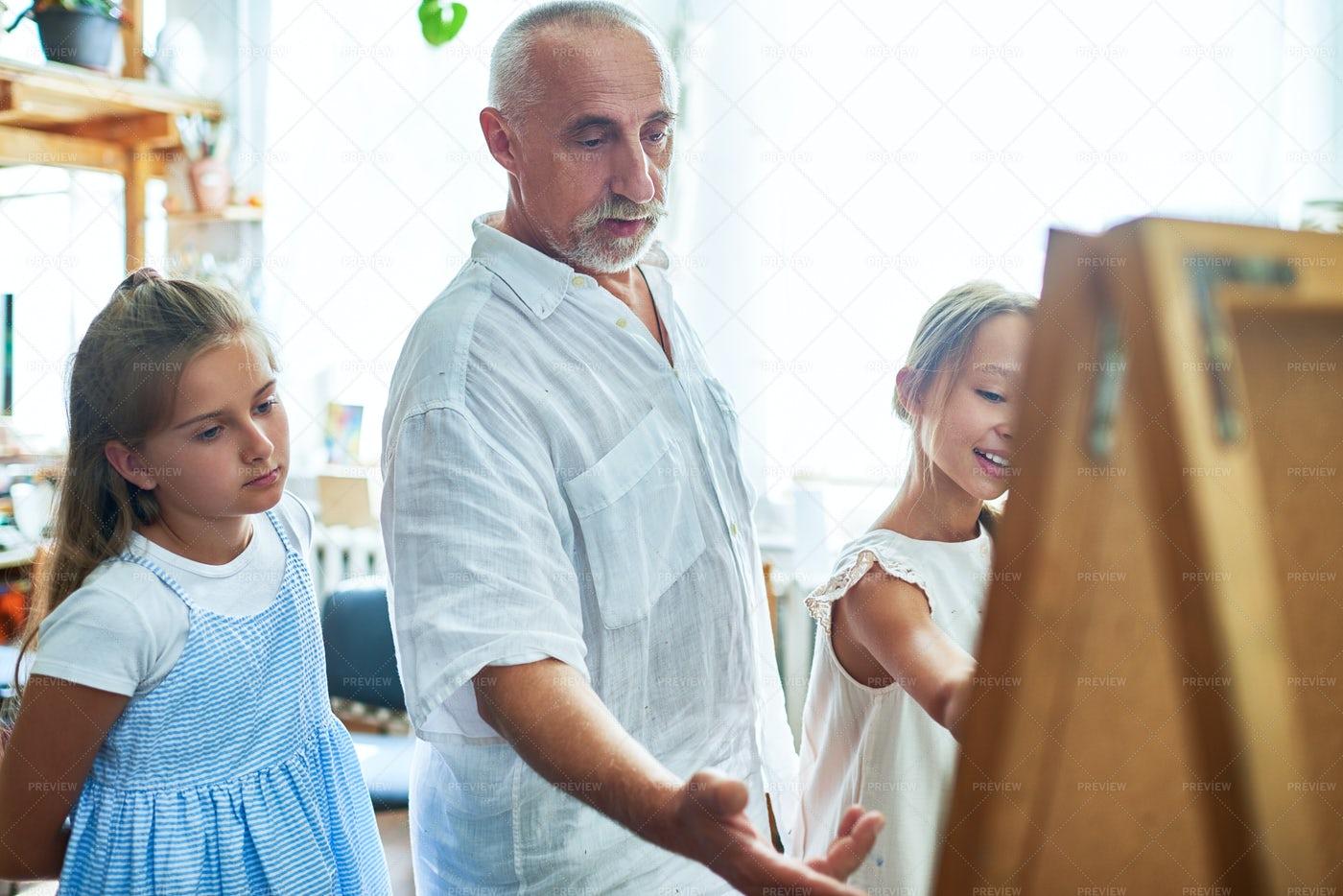 Senior  Art Teacher Helping Kids In...: Stock Photos
