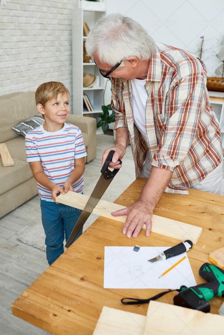 Little Boy Helping Senior Carpenter: Stock Photos