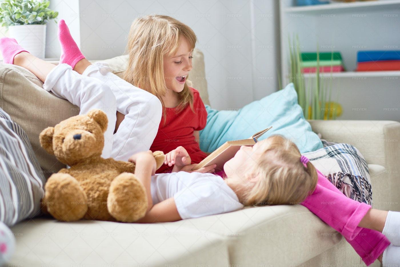 Little Sisters Reading Aloud: Stock Photos