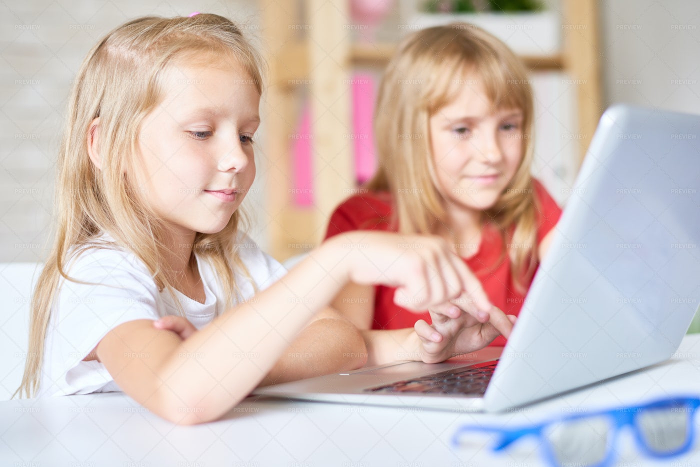 Cute Sisters Using Laptop: Stock Photos