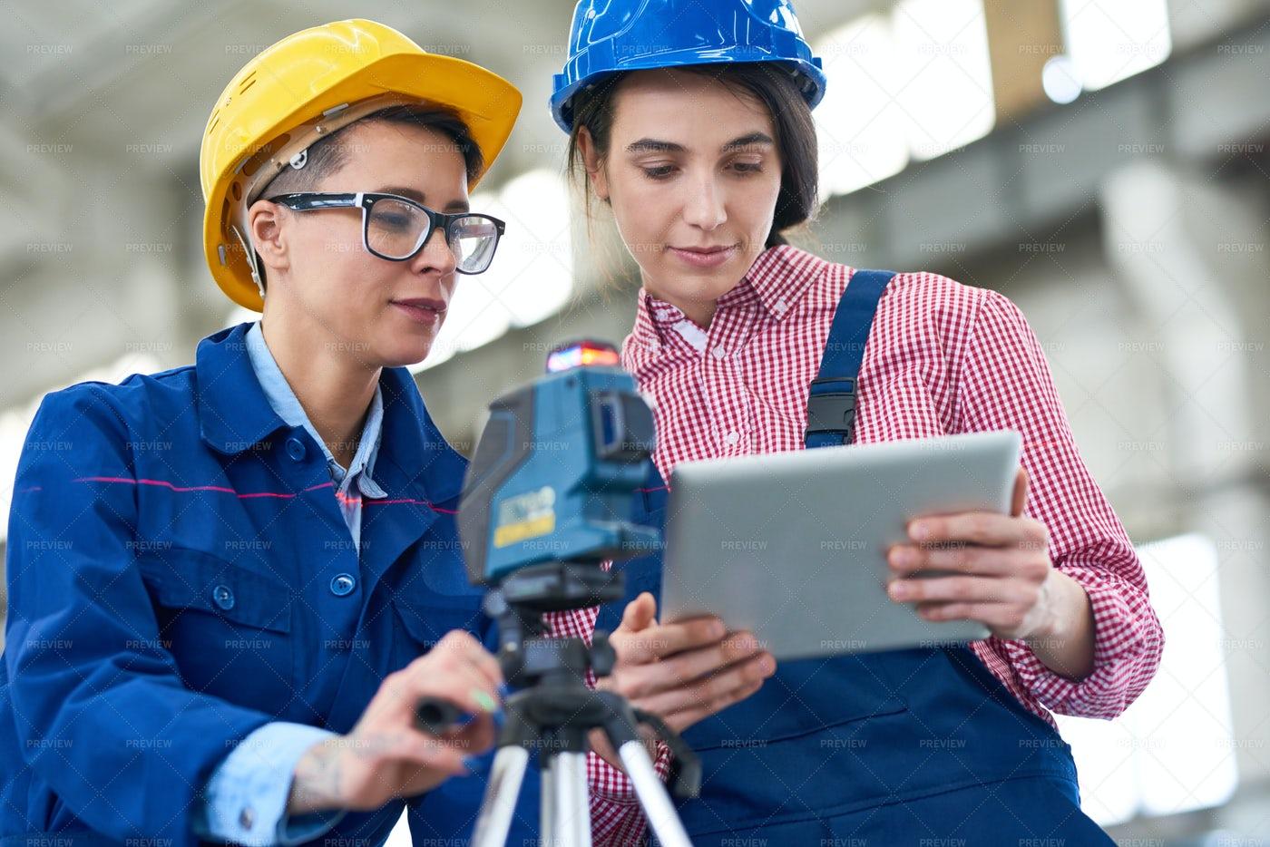 Pretty Surveyors Focused On Work: Stock Photos