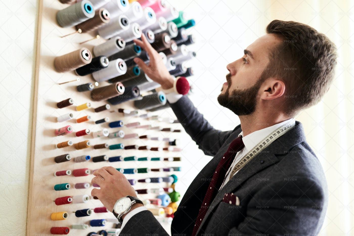 Handsome Tailor Choosing Thread...: Stock Photos